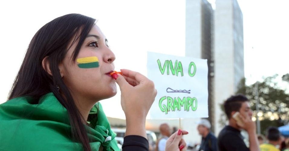 """21.mar.2016 - Manifestante levanta cartaz com os dizeres """"Viva o grampo"""" durante protesto em Brasília (DF), que reuniu cerca de 2000 pessoas, segundo levantamento da Polícia Militar"""