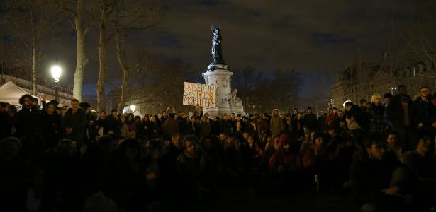 """Simpatizantes do movimento """"Nuit Debout"""" fazem vigília na praça da República, em Paris; cartaz diz: """"crise de um sistema mortífero"""""""