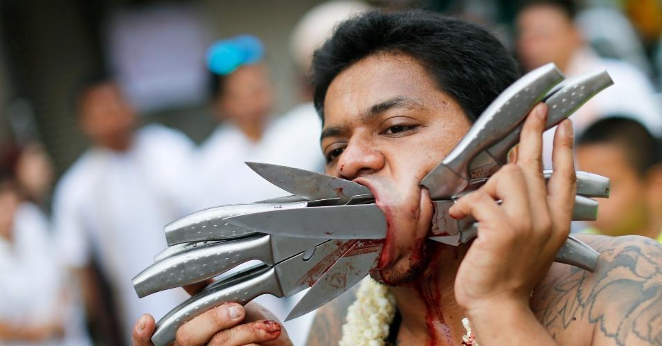 5.out.2016 - Devoto do santuário Ban Tha Rue caminha com dez facas atravessando a bochecha em procissão durante festival religioso em Phuket, na Tailândia
