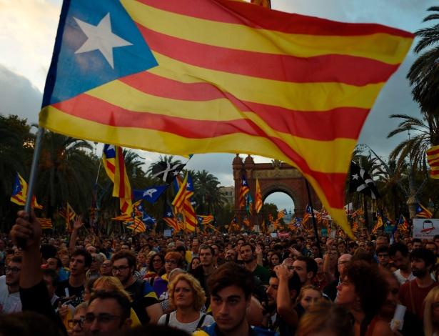 10.out.2017 - Apoiadores da independência da Catalunha ouvem o pronunciamento do líder catalão Carles Puigdemont em um telão no Arc de Triomf, em Barcelona