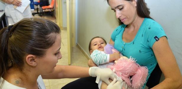 Criança toma vacina na rede pública