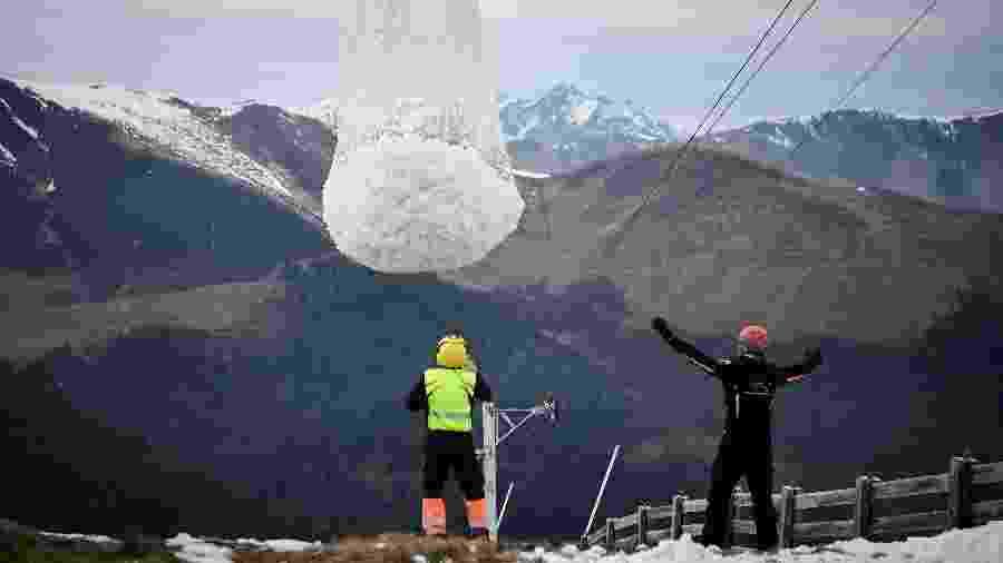 Funcionários de estação de esqui nos Pirineus participam de ação com helicóptero para retirar neve do topo de uma montanha - Anne-Christine Poujoulat/AFP