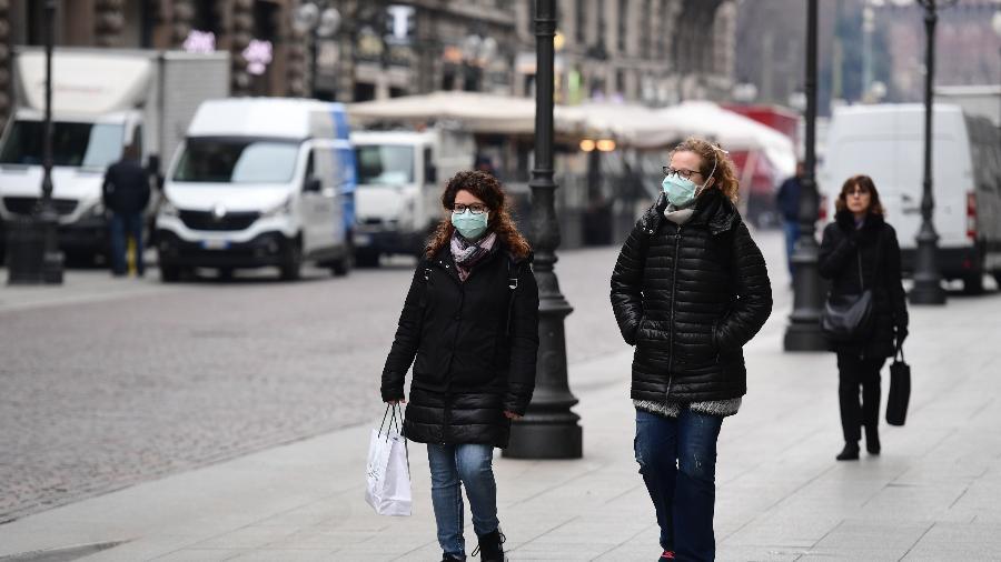 Pedestres caminham no centro de Milão, na Itália, usando máscaras devido à epidemia do novo coronavírus - Miguel Medina/AFP