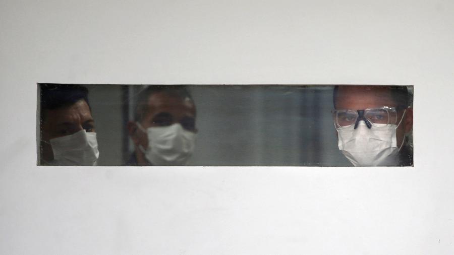 Homens com máscara olham por janela de hospital em São Paulo - RAHEL PATRASSO
