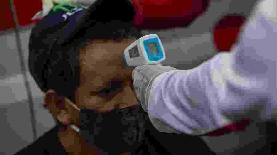 Voluntário da Cruz Vermelha mede temperatura de homem na Nicarágua - AFP