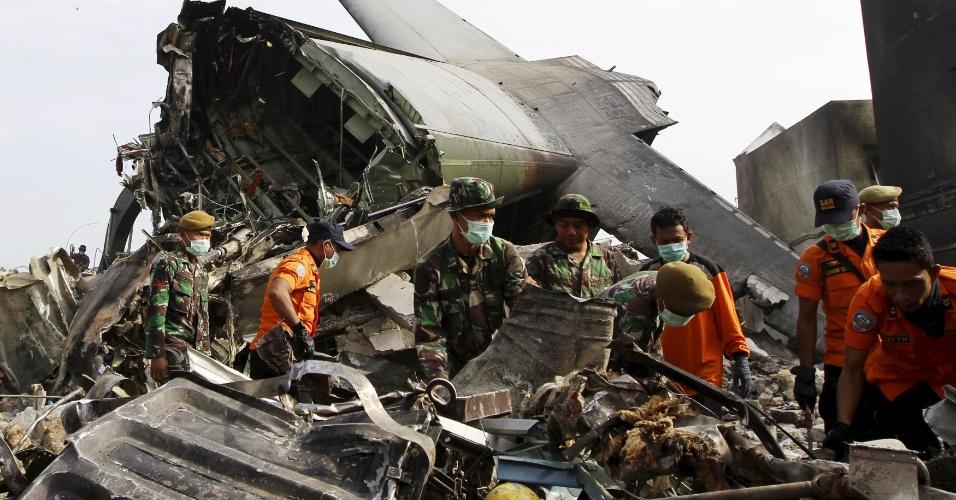 1.jul.2015 - Soldados e equipe de resgate trabalham entre os destroços do avião de transporte militar que caiu ontem na Indonésia em uma área residencial de Medan, no norte da ilha de Sumatra