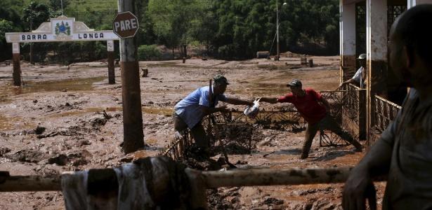 Homem retira objetos de dentro de casa em MG após rompimento de barragem em 2015