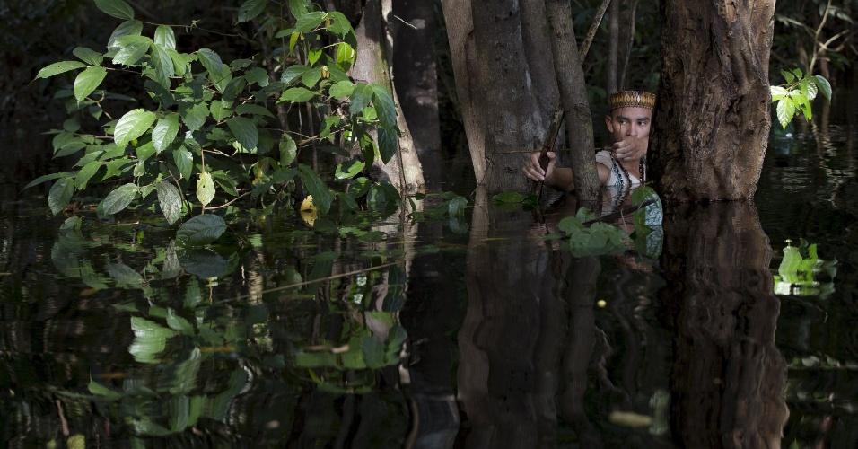 9.mai.2015 - Índio da etnia Kambeba, Sonho Braga aponta sua flecha na floresta perto da aldeia Três Unidos, no Amazonas