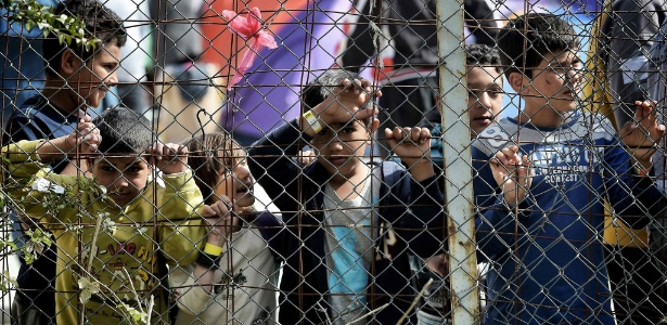 Grupo de crianças olha através de cerca em campo de refugiados na ilha de Lesbos, na Grécia