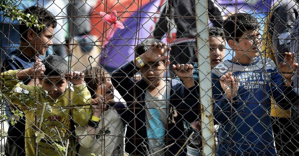 3.abr.2016 - Um grupo de crianças olha através de cerca em campo de refugiados na ilha de Lesbos, na Grécia. Alguns migrantes serão obrigados a retornar da Grécia para a Turquia após um acordo da União Europeia - mais de 51 mil refugiados estão na Grécia aguardando para entrar em outras nações da Europa
