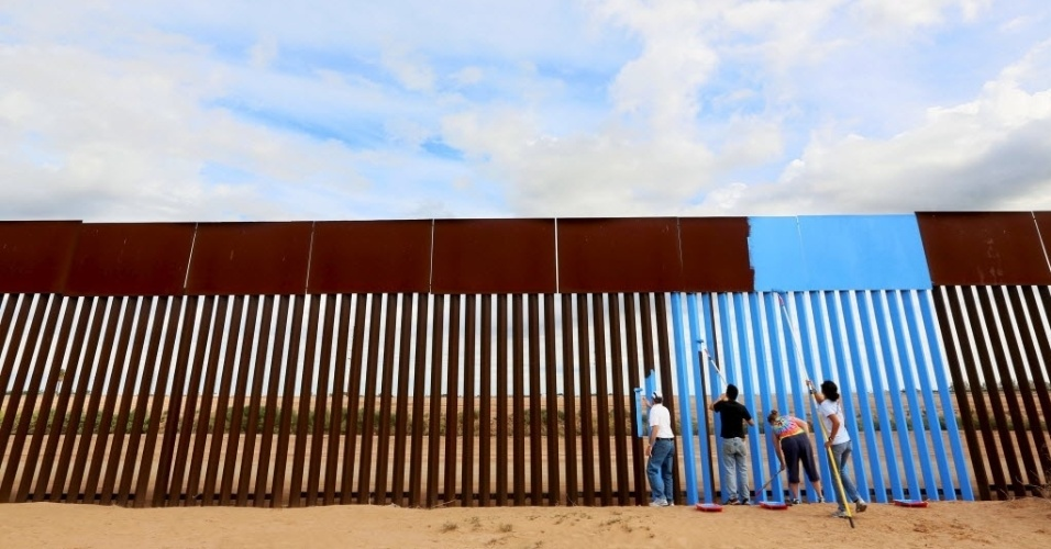 """9.abr.2016 - Um grupo de voluntários pintam de azul o lado mexicano da cerca que separa o país dos Estados Unidos. A pintura, feita neste sábado (9), faz parte de uma intervenção artística chama """"Apagando a Fronteira"""" e tenta dar a ilusão de invisibilidade à cerca"""