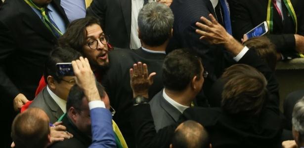17.abr.2016 - O deputado Jean Willys (PSOL-RJ) cospe em Jair Bolsonaro (PSC-RJ) (de costas com o braço levantado) durante a sessão da Câmara dos Deputados. Em seguida, o filho de Jair, Eduardo, cuspiu em Jean