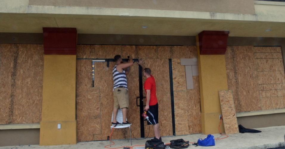 6.out.2016 - Proprietários de loja protegem a entrada do estabelecimento, localizado em Titusville, antes da passagem do furacão Matthew pelo Estado