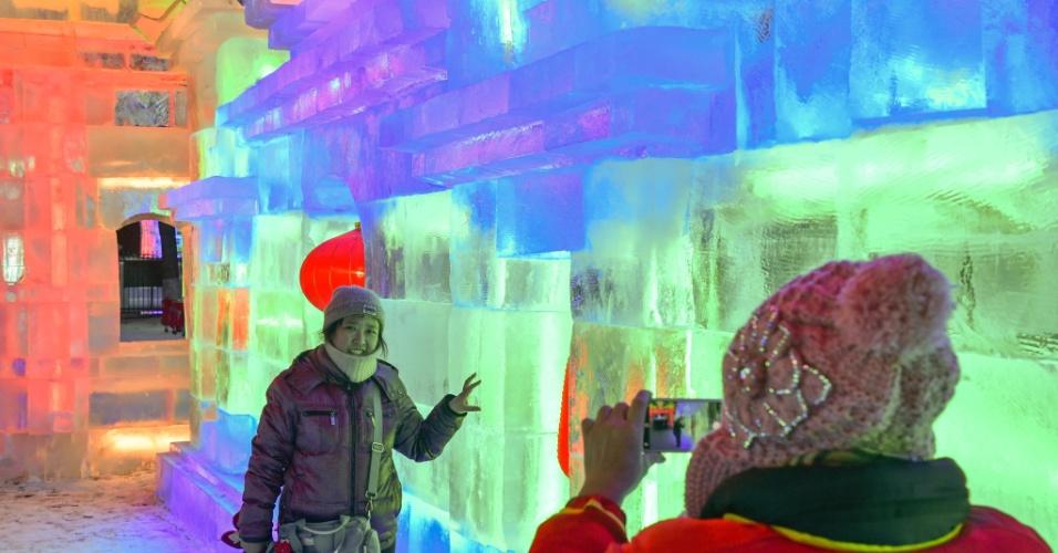 26.dez.2016 - Visitantes tiram fotos no 43º festival de lanternas de gelo de Harbin, na China. O evento com as lanternas iluminadas por luzes coloridas ocorre na província de Heilongjiang