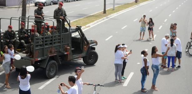 Moradores tiram fotos com os militares que estão trabalhando na segurança da orla da praia de Camburi, em Vitória (ES)