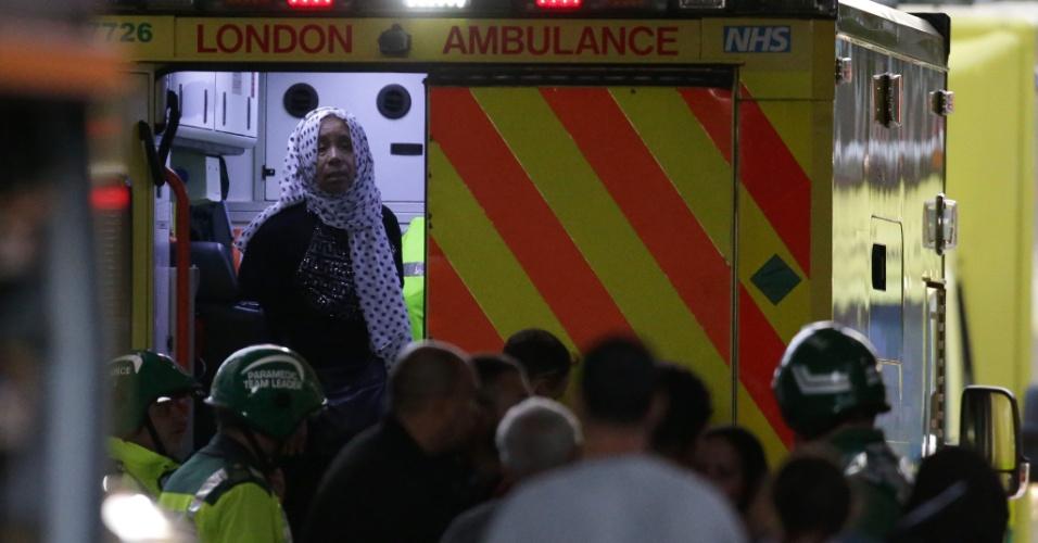 14.jun.2017 - Moradora é atendida em ambulância depois de ser retirada da Grenfell Tower, que pegou fogo na madrugada desta quarta