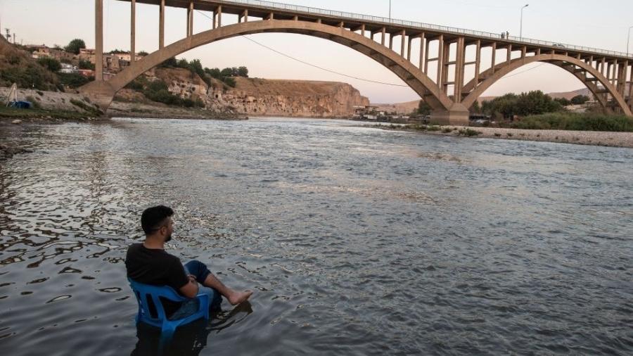 A calma antes da tormenta: um homem descansa nas margens do rio Tigre, enquanto as águas sobem lentamente para submergir seu povoado - Getty Images