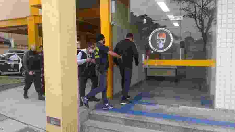 Policial militar (de costas, no meio da foto) foi preso preventivamente acusado de chefiar uma milícia em Nova Iguaçu (RJ)  - Divulgação/Polícia Civil do Rio