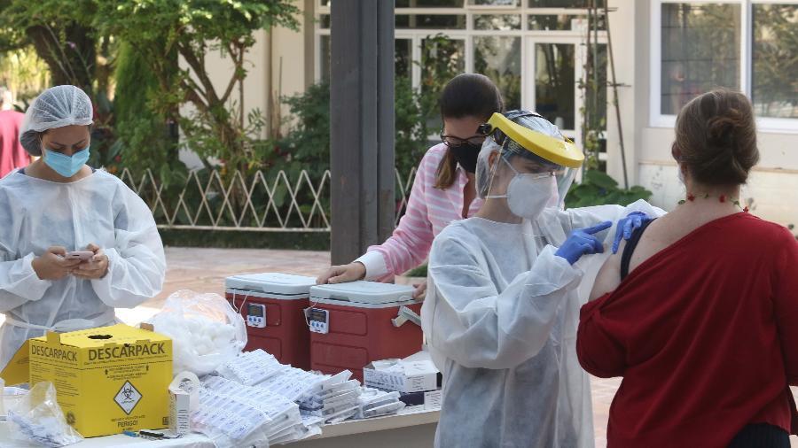 Moradores da cidade de Botucatu, no interior de São Paulo, recebem o imunizante contra a covid-19, da Oxford/Astrazeneca, neste domingo, 16 - Vitor Orsola/Estadão Conteúdo