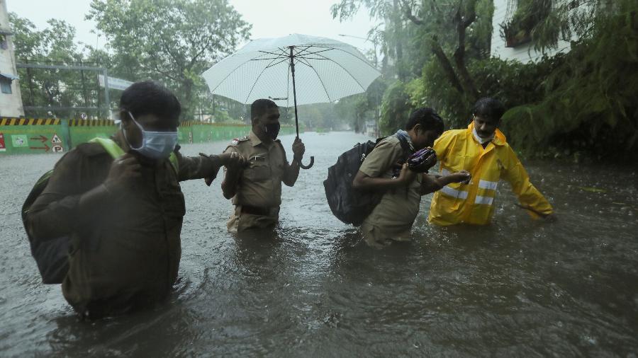 Trabalhadores ajudam pessoas a atravessar uma rua inundada após chuvas causadas pelo ciclone Tauktae em Mumbai, Índia - REUTERS / Francis Mascarenhas