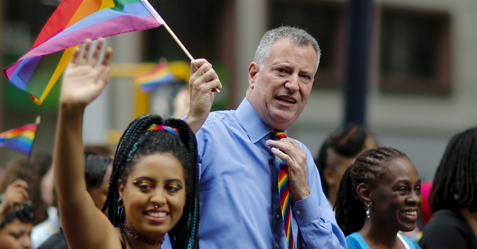 28.jun.2015 - O prefeito de Nova York, Bill de Blasio, segura uma bandeira com as cores do arco-íris ao lado da sua mulher, Chirlane, e sua filha Chiara, durante Parada do Orgulho Gay, ao longo da 5ª Avenida, em Manhattan, na cidade de Nova York (EUA), neste domingo (28). Uma decisão da Suprema Corte dos Estados Unidos legalizou na sexta-feira (26) o casamento entre pessoas do mesmo sexo, ao derrubar vetos estaduais à união homossexual