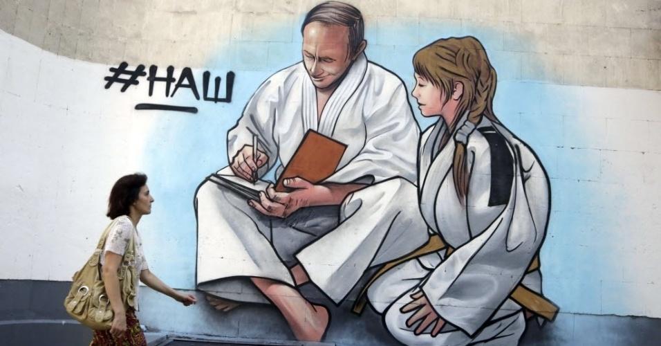 4.set.2015 - Pedestre passa por parede com um grafite do presidente da Rússia, Vladimir Putin, vestindo um quimono, na cidade de Yalta, na Crimeia. O território está no centro da atual disputa entre a Ucrânia e a Rússia