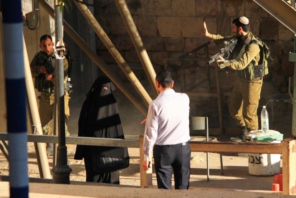 22.set.2015 - A estudante palestina Hadeel al-Hashlamon, 18, sendo interrogada no checkpoint em Hebron. Ela foi morta a tiros, minutos depois, por um dos militares. A versão do Exército é que ela ameaçou-o com uma faca. Testemunhas dizem que ela não queria ser revistada por homens. Após a divulgação das fotos, o fotógrafo brasileiro, autor da sequência, decidiu sair de Israel