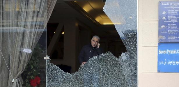 Investigador da polícia é visto através de vidro quebrado em hotel atacado por homens armados no Cairo, no Egito