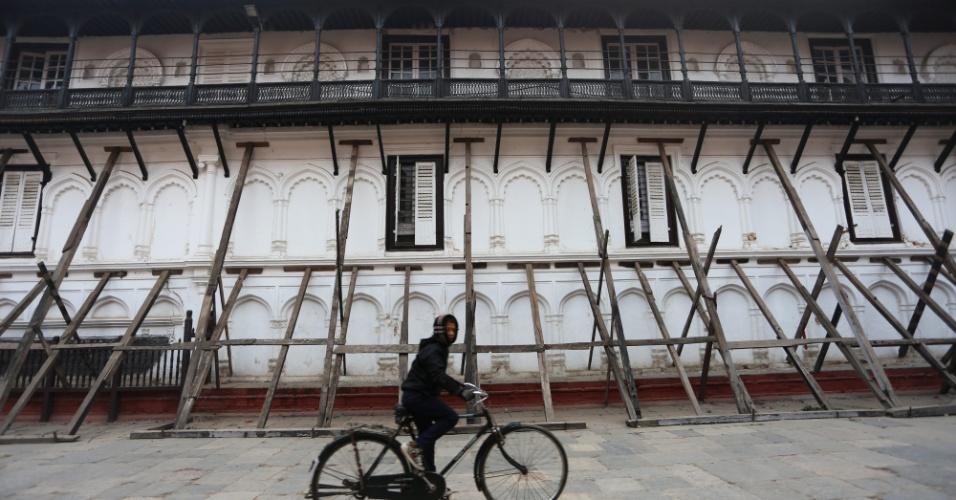 16.jan.2016 - Homem pedala em frente ao palácio Hanumandhoka, em Katmandu, no Nepal, edifício que foi afetado pelo terremoto de abril de 2015. Nove meses após o abalo, o governo do Nepal começou neste sábado (16/01) o processo de reconstrução do país