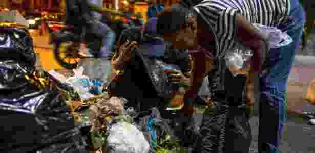 Pessoas procuram restos de alimentos no lixo, em Caracas, Venezuela - Miguel Gutiérrez/ Efe