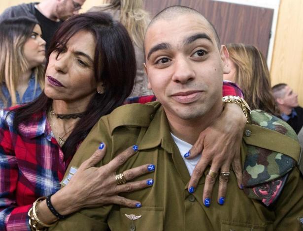 O soldado israelense Elor Azaria é abraçado pela mãe, Oshra, no começo de audiência judicial em Tel Aviv