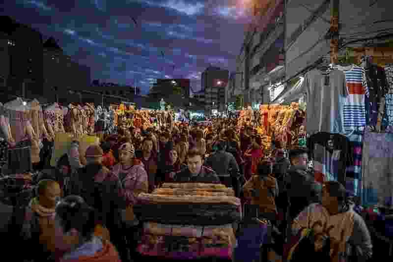 28.nov.2017 - Lotadíssima e localizada no centro de São Paulo, a Feirinha da Madrugada é a maior feira informal da América do Sul. É composta em sua maioria por vendedores de diversas origens, da Bolívia à China. Em busca de roupas baratas, os compradores vêm do interior de São Paulo e vários Estados - Flavio Forner/The Guardian
