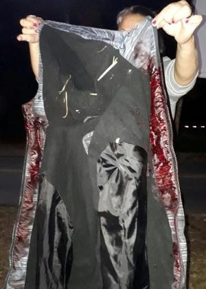 Manifestante segura blusa com sangue de uma das vítimas do ataque a acampamento