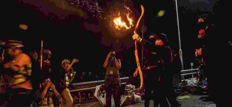 Manifestantes usam flechas em chamas em Hong Kong - Anthony WALLACE / AFP