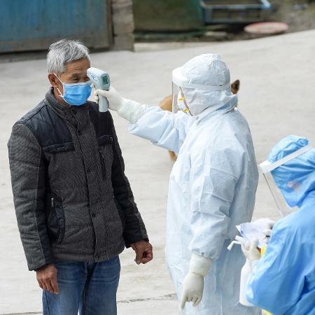 7.fev.2020 - Agentes de saúde medem a temperatura de morador na cidade de Taojiazhen, no sudoeste da China, em meio à epidemia - Liu Chan/Xinhua