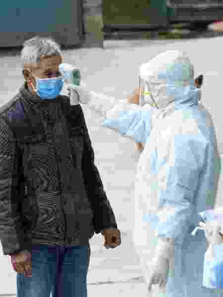 7.fev.2020 - Agentes de saúde medem a temperatura de morador na cidade de Taojiazhen, no sudoeste da China - Liu Chan/Xinhua