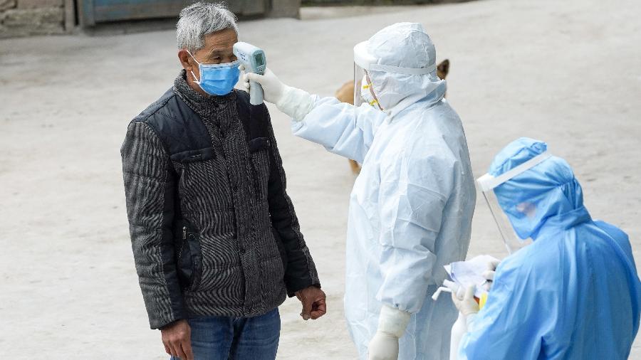 7.fev.2020 - Agentes de saúde medem a temperatura de morador na cidade de Taojiazhen, no sudoeste da China, em meio à epidemia do novo coronavírus - Liu Chan/Xinhua