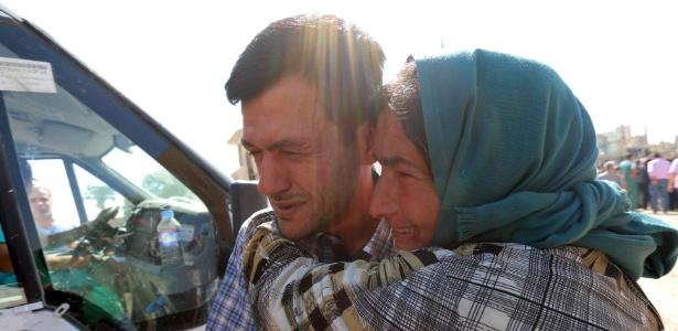 4.set.2015 - Abdullah Kurdi chora ao lado de parente durante funeral de seus filhos e sua mulher, em Kobani, na Síria