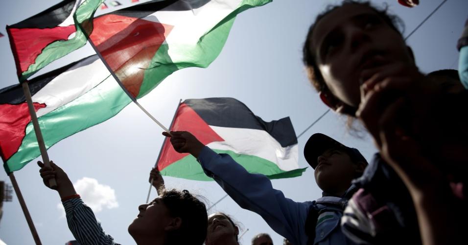 30.set.2015 - Palestinos agitam bandeiras nacionais em Ramallah enquanto assistem discurso do presidente Mahmoud Abbas nas Nações Unidas. Resolução adotada recentemente pela ONU permitiu o hasteamento dos símbolos nacionais palestino e do Vaticano na sede da entidade, em Nova York