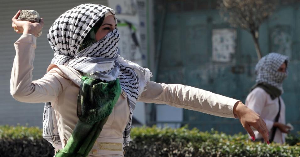 13.out.2015 - Uma estudante palestina da Universidade de Hebron joga pedra em direção aos soldados israelenses e da polícia de fronteira durante confrontos entre palestinos e forças de segurança israelenses em Hebron, na Cisjordânia. Manifestantes palestinos bloquearam a principal entrada ao norte da cidade com pedras e pneus. A crescente onda de agitação tem levantado temores sobre uma terceira Intifada, o levante palestino feito em grande escala, que deve aumentar a violência de ambos os lados do conflito