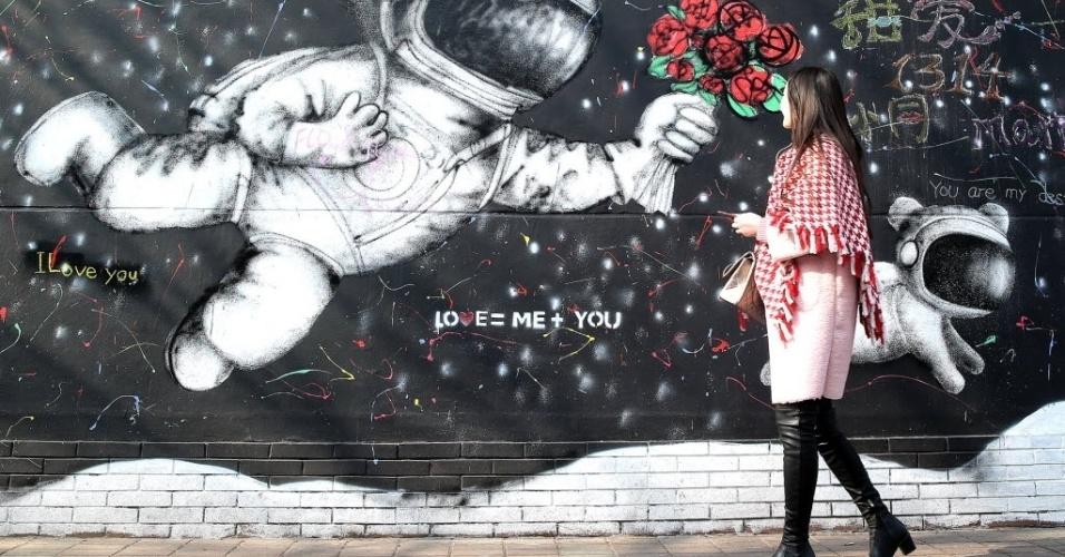 9.jan.2016 - Mulher passa por grafite de astronauta que parece entregar flores para os pedestres em Xangai, na China