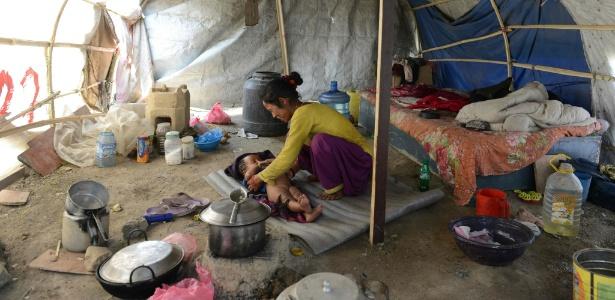 Nepalesa que teve a casa destruída por terremoto cuida de seu bebê na tenda onde mora com o marido, em Ramechhap, no Nepal