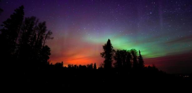 O incêndio florestal que atinge parte da província canadense de Alberta ilumina o céu de laranja, justo abaixo da Aurora Boreal