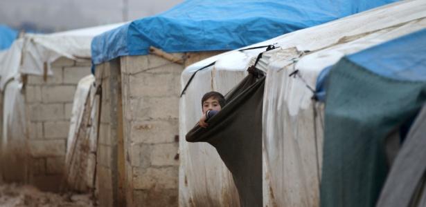 26.dez.2016 - Criança síria olha para fora de sua tenda em um campo de refugiados na fronteira entre Síria e Turquia