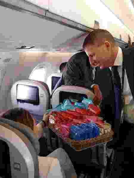 16.out.2019 - Durante primeiro voo do mundo com passageiros do Embraer E195-E2, John Rodgerson, presidente da Azul, assumiu o papel de comissário de bordo e serviu snacks a todos os passageiros - Vinícius Casagrande/UOL