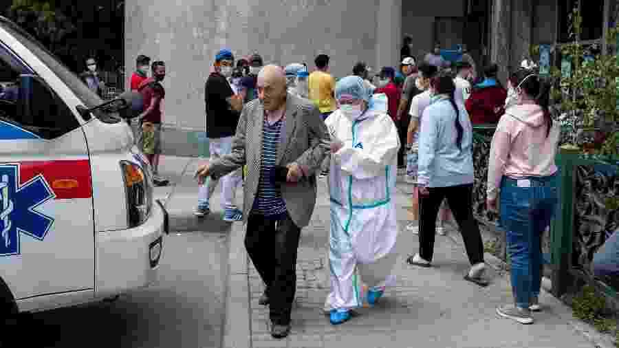 Médico ajuda um idoso rumo à uma ambulândia em frente a um centro médico para coronavírus em Bishkek - DANIL USMANOV / AFP