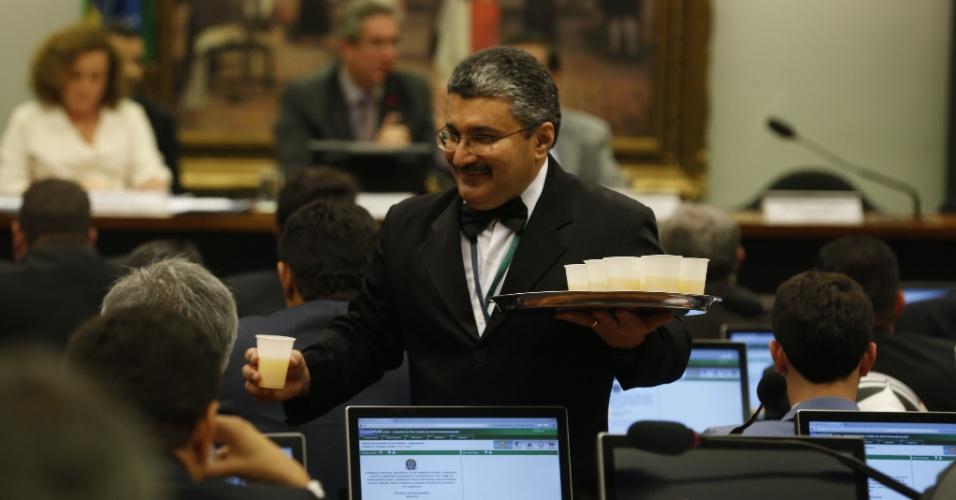 4.abr.2016 - Garçom entrega suco de maracujá aos deputados durante audiência da comissão especial do impeachment, na Câmara dos Deputados, em Brasília