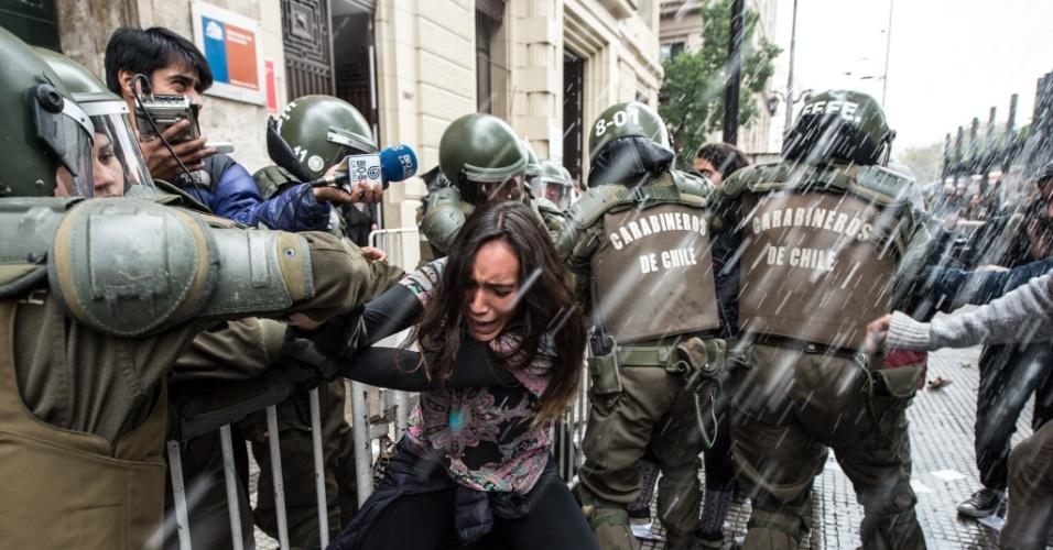 28.abr.2016 - Policias prendem estudante que protesta na frente do Ministério da Educação por uma reforma educacional no Chile. O ato foi convocado pela Federação de Estudantes do Chile