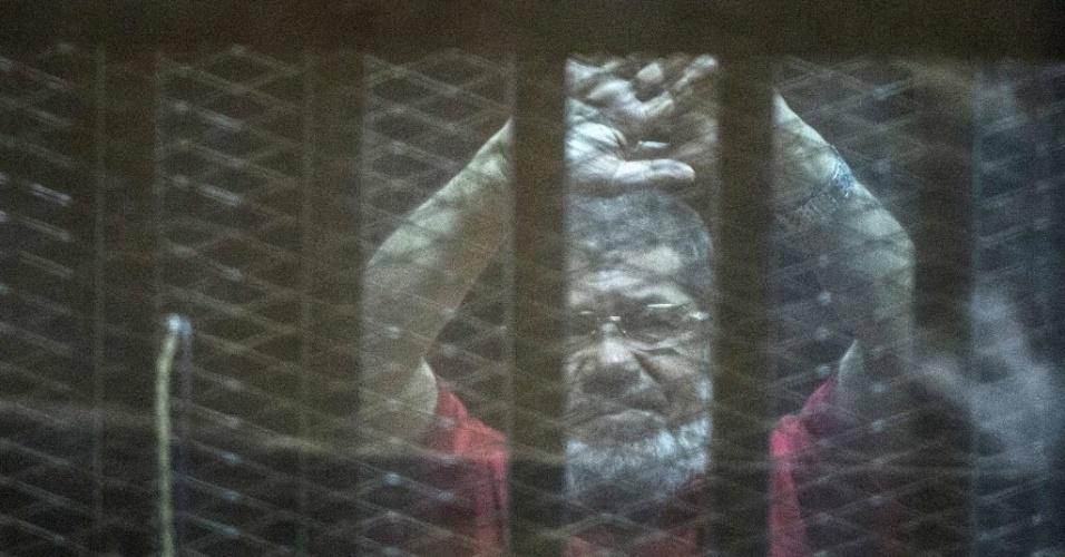 """7.mai.2016 - O ex-presidente do Egito Mohamed Morsi, que foi deposto após um golpe militar em 2013, gesticula em cela durante julgamento no Cairo. O tribunal egípcio determinou neste sábado (7) pena de morte para seis réus em julgamento sobre crimes de espionagem. Mursi não recebeu a pena capital. Ele foi julgado ao lado de outras 10 pessoas pela acusação de supostamente ter repassado """"documentos de segurança nacional"""" ao Catar. Este é o quarto processo contra Mursi, membro da Irmandade Muçulmana, classificada como organização """"terrorista"""" pelas autoridades. O ex-presidente já foi condenado à morte, prisão perpétua e a 20 anos de prisão em três processos distintos"""