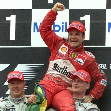 1.ago.00 - GP da Alemanha: Rubens Barrichello, da equipe Ferrari, comemora a vitória no pódio, erguido por Mika Hakkinen (E), e David Coulthard, ambos da McLaren - REUTERS/Reinhard Krause